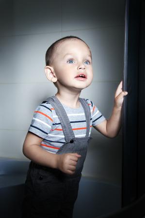 cabine de douche: Adorable petit gar�on � l'�ge de deux dans un T-shirt ray� regardant debout dans une cabine de douche Banque d'images
