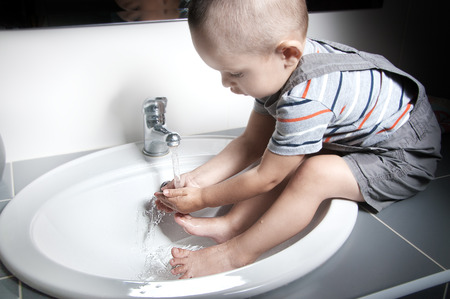 Adorable  little boy at the age of two in a striped T-shirt  looking at the flow of water in the sink and washing her hands and feet in the sink Stock Photo
