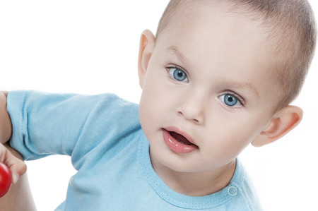 Adorable  little boy at the age of two in a blue T-shirt  looking at the camera on a white background