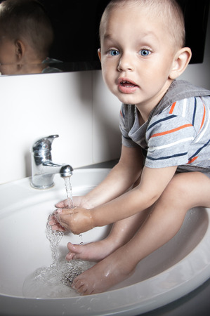 Adorable  little boy at the age of two in a striped T-shirt  looking up washing his hands and feet in the sink
