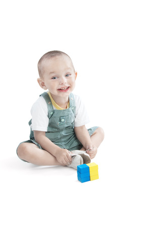 Adorable smiling  little boy at the age of two in a romper and white T-shirt  looking at the camera on a white background with  Ukrainian flag composed of childrens blue and yellow blocks Stock Photo