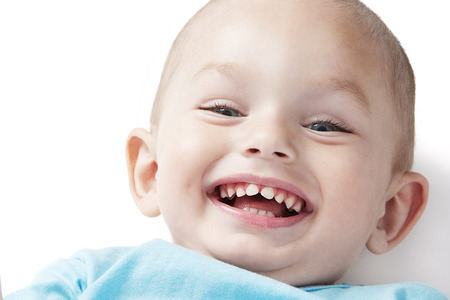 Adorable smiling  little boy at the age of two in a blue T-shirt  looking at the camera on a white background