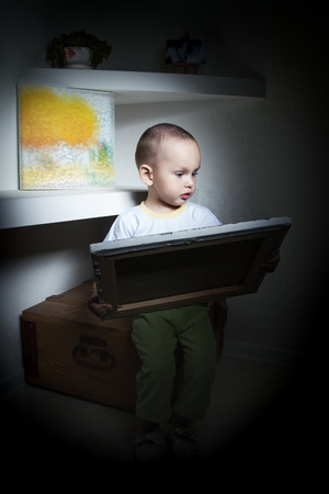 Adorable  little boy at the age of two in a white T-shirt  lookingat the picture
