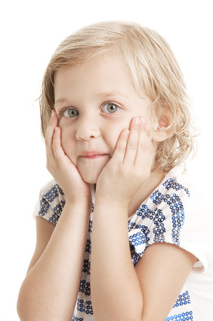 Adorable  little giirl  putting her hands to the face and looking at the camera on white background  Stock Photo
