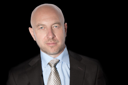 Bald man in a suit and tie on a black background Stock Photo
