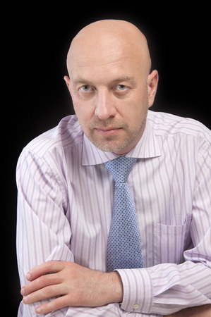 Man in a striped shirt and tie sitting with arms folded, looking at the camera on the black background