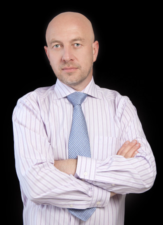 Man in a striped shirt and tie standing with arms folded, looking at the camera on the black background