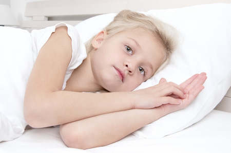 Adorable little girl looking at the camera  lying in bed