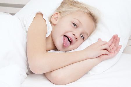 かわいい女の子を彼女の舌でベッドで横になっているカメラ目線