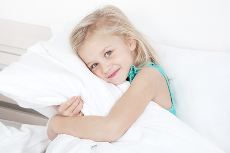 Adorable little girl looking at the camera and hugging a pillow sitting on a bed on the background of a rough wall with texture Stock Photo