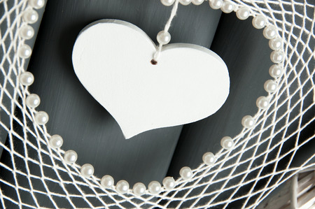 Handmade white lace heart dream catcher with pearls on gray background close up