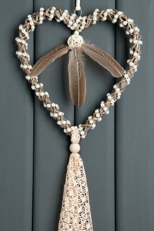 Handmade beige lace heart dream catcher with pearls on gray background. Stock Photo