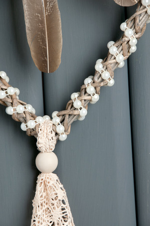 Handmade beige lace heart dream catcher with pearls on gray background close up