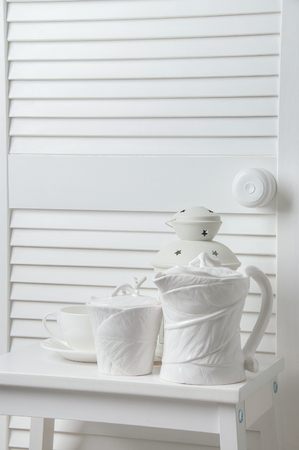 teaset: White bedroom decor with candle, candlesticks and  tea-set