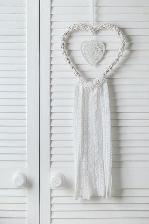 l natural: White heart dream catcher with white lace in bedroom interior. Wedding decor