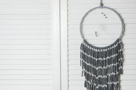 jalousie: Gray white dream catcher in bedroom interior . Bedroom decor close-up