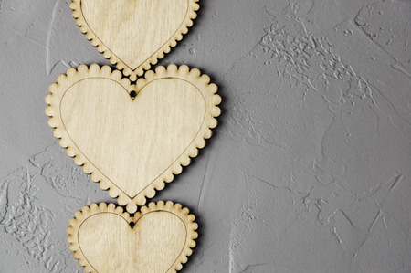 Wooden hearts on gray background. Texture of plaster