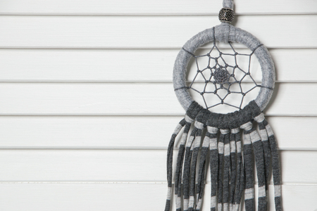 Gray dream catcher on white door. Bedroom decor