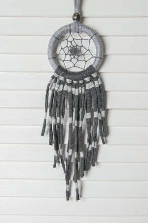 talisman: Atrapasueños gris en la puerta blanca. Decoración del dormitorio Foto de archivo