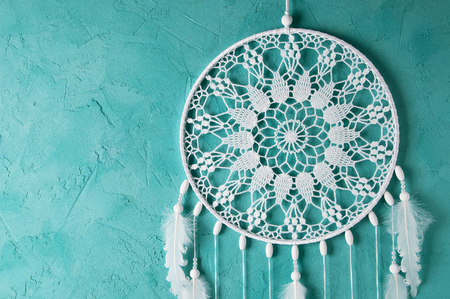 White dream catcher on turquoise textured background. Texture of concrete.