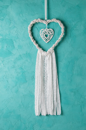 Wedding white heart dream catcher on turquoise textured background. Texture of concrete.