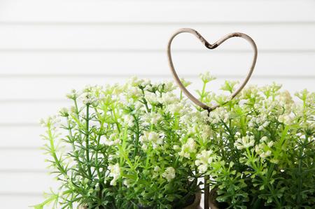 jalousie: Shabby metal heart and flowers on door background . Bedroom decor