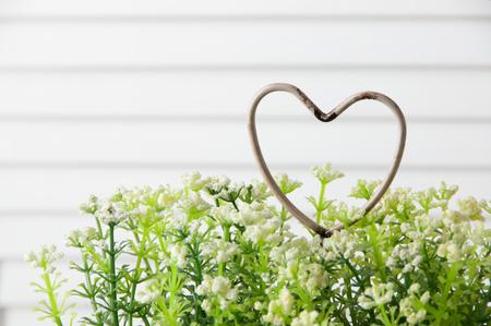 Shabby metal heart and flowers on door background . Bedroom decor