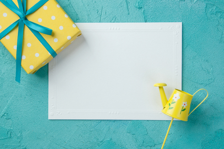 Yellow white polka dot box, blank note, watering can on turquoise textured background.Top view and copy space for text Stock Photo