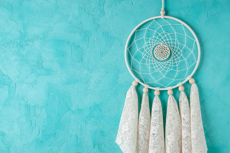 Lace cream dream catcher on turquoise textured background. Texture of concrete.