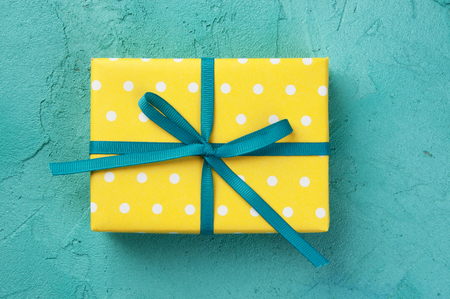 Top view of yellow white polka dot box and turquoise bow on turquoise textured background. Texture of concrete.