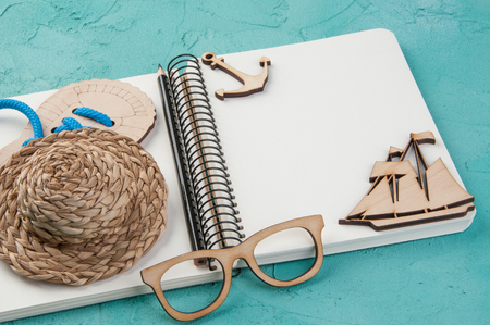 Blank notebook, hat, wooden boat and glasses on turquoise background. Travel and adventure concept, journey diary