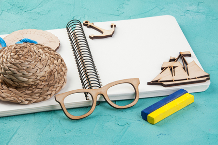 Blank notebook, hat, crayons, wooden boat and glasses on turquoise background. Travel and adventure concept, journey diary Stock Photo