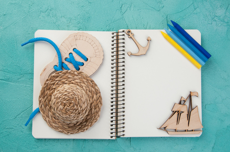 Top view of open blank notebook, wooden boat , hat and pencils on turquoise background. Travel and adventure concept, journey diary Stock Photo