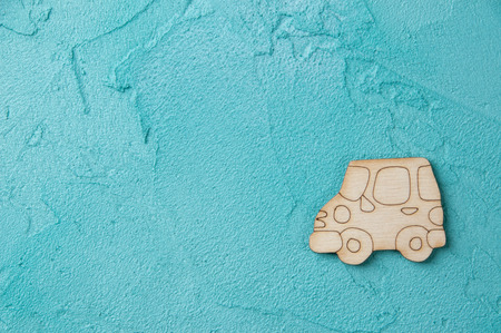 Turquoise textured desk with wooden car. Texture of concrete