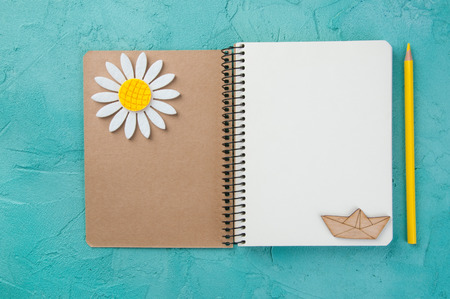 Top view of open blank notebook, wooden boat, pemcil and felt chamomile on turquoise background. Travel and adventure concept, journey diary