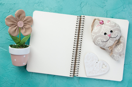 Top view of open blank notebook, wooden heart ,toy and flower in a pot on turquoise background. Stock Photo