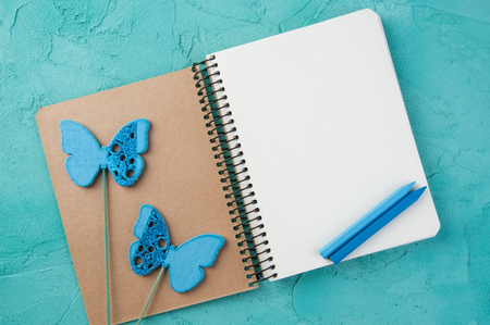 Top view of open blank notebook, wooden butterflies and pencils on turquoise background. Travel and adventure concept, journey diary Stock Photo