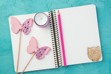 Top view of open blank notebook, wooden owland butterflies, candle and  pink pencil on turquoise background. Travel and adventure concept, journey diary Stock Photo