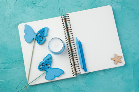Top view of open blank notebook, wooden star and butterflies, candle and pencils on turquoise background. Travel and adventure concept, journey diary Stock Photo