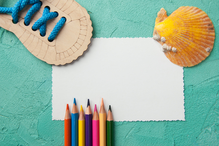 White blank note, pencils and orange shell on turquoise textured background.Top view and copy space for text