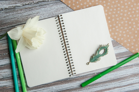 Kraft paper white polka dot, notebook  with a narcissus,metal feather and green pencils on wooden  background.Top view and copy space for text
