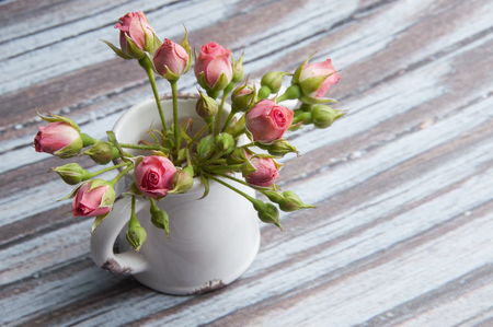 Pink mini roses in a jar on wooden textured background.