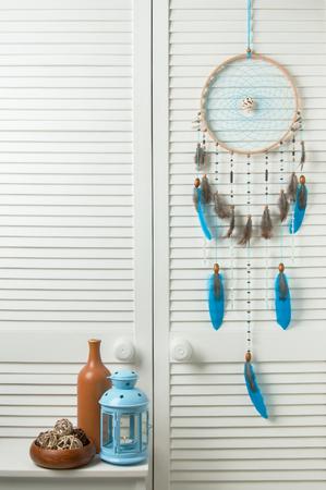 closet door: Turquoise dream catcher with blue candlestick and brown bottle in bedroom interior . Bedroom decor