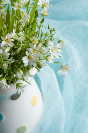 White wild flowers in a jug on blue ranner close up