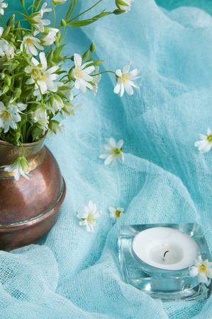 White wild flowers in a brass jug and candle on blue ranner close up Stock Photo