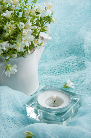 White wild flowers in a jug and candle on blue ranner close up Stock Photo
