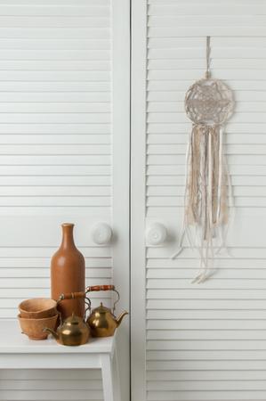 Beige dream catcher with brown bottle, cups and brass teapots on the closet door background. Bedroom decor.