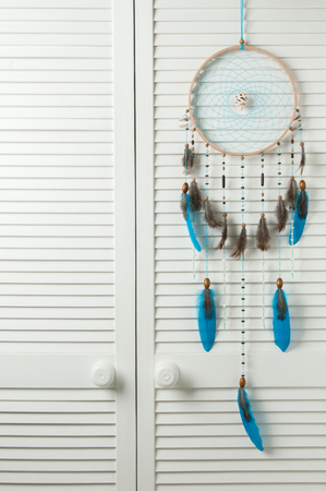 Turquoise dream catcher in bedroom interior . Bedroom decor