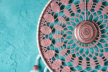 Pink ash crochet doily dream catcher close up on aquamarine textured background. Texture of concrete, copy space for text