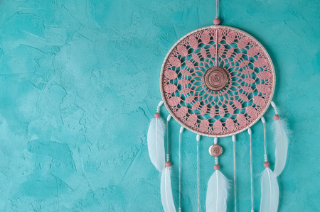 Pink ash crochet doily dream catcher on aquamarine textured background. Texture of concrete, copy space for text